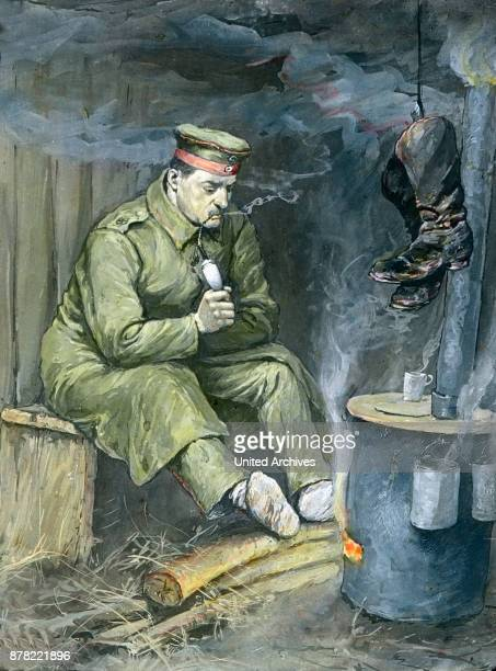A German soldier warming his cold feet by a fire