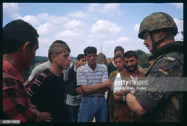A German soldier with NATO forces speaks with a group of Kosovar Albanians during the Yugoslavian Civil War In the 1990s the Serbian government...