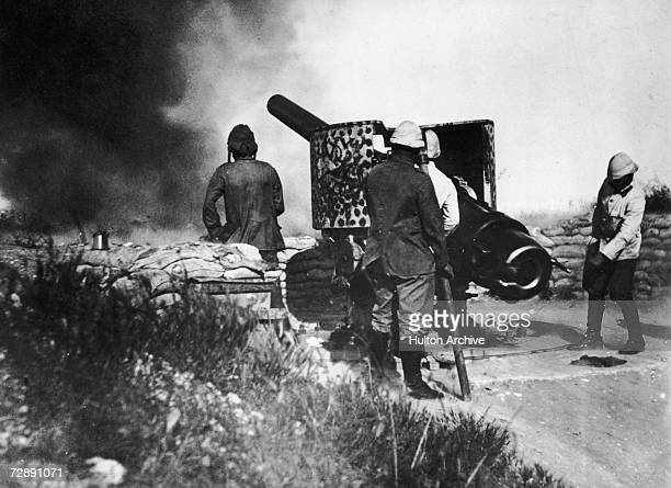 German soldiers firing a sixinch gun at an English Observation post in Africa during World War I