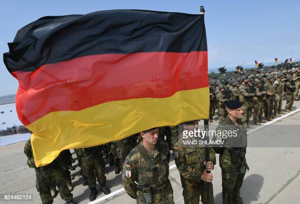 German soldiers holding Germany's national flag attend the opening ceremony of the joint multinational military exercise 'Noble Partner 2017' at the...