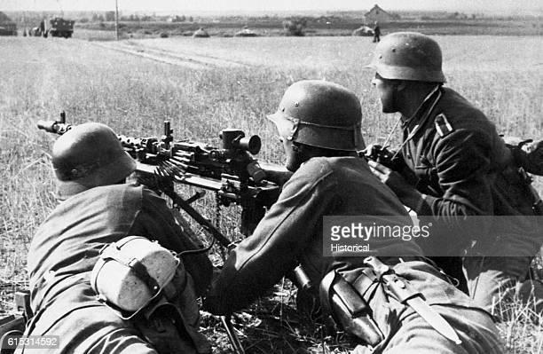 German soldiers man a machine gun in a rural area during a European campaign