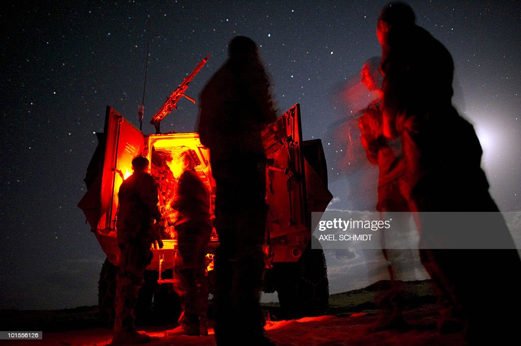German soldiers stannd outside a infantry fighting vehicle, some 30 kilometres north of Kunduz, Afghanistan on May 18, 2010. The soldiers are on a three-day-mission with Afghan police and army, during which they patrol through a Taliban-controlled region.