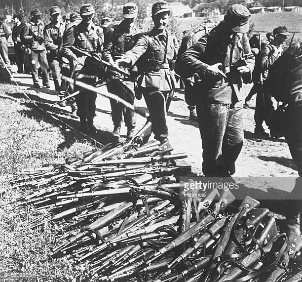 German soldiers surrendering at the DanishGerman border throwing their firearms in a pile as they file by | Location Border of Denmark and Germany