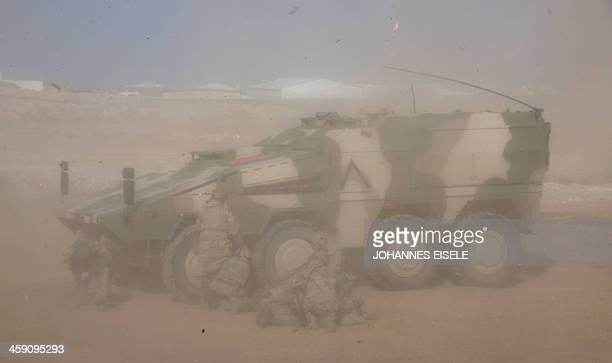 German soldiers take cover from rotor wash beside a Boxer armoured fighting vehicle at Camp Marmalin MazareSharif on December 23 2013 About 3000...