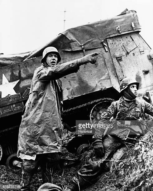 German soldiers take cover in a ditch beside a disabled American tank during the Battle of the Bulge Belgium December 1944