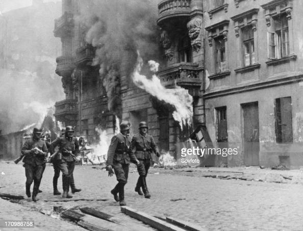 German soldiers walking by fires set in the warsaw ghetto which was burned to the ground after the uprising world war ll poland 1944