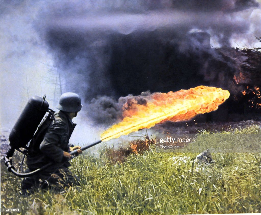 A German solider aims a backpack flamethrower across a field of tall grass, Soviet Union, 1941 or 1942. The image was originally published as 'Das Heer im Grossdeutschen Freiheitskampf' (translated as 'The Army in the Greater German Freedom Struggle'), a collection of 50 plus images taken by the German Army's combat photography unit (Propagandakompanie) during the German invasion of the Soviet Union.