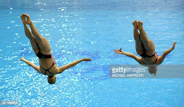 German sycro diver Ditte Kotzian jumps next to her teammate Heike Fischer during a training session at the National Aquatics Center a few days before...
