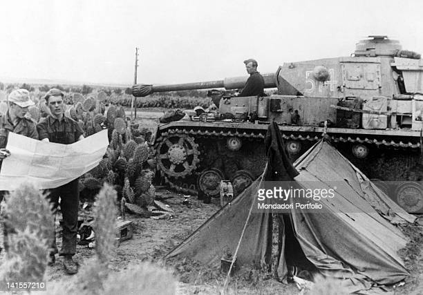 German tank parked at the Kasserine Pass near the crews tent while two tank drivers consult a map Tunisia February 1943