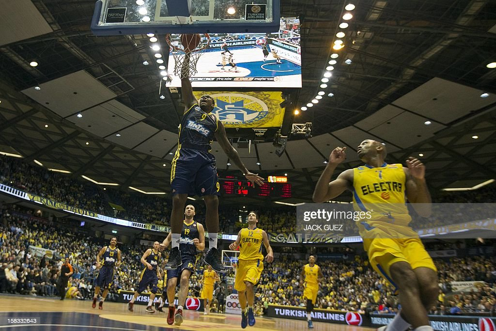German team Alba Berlin's US forward Deon Thompson (L) goes for a dunk as Maccabi Tel Aviv US guard Ricky Hickman (R) looks on during their Euroleague Playoff basketball match, game 10 group B, on December 13, 2012 at the Nokia stadium in the Mediterranean coastal city of Tel Aviv.