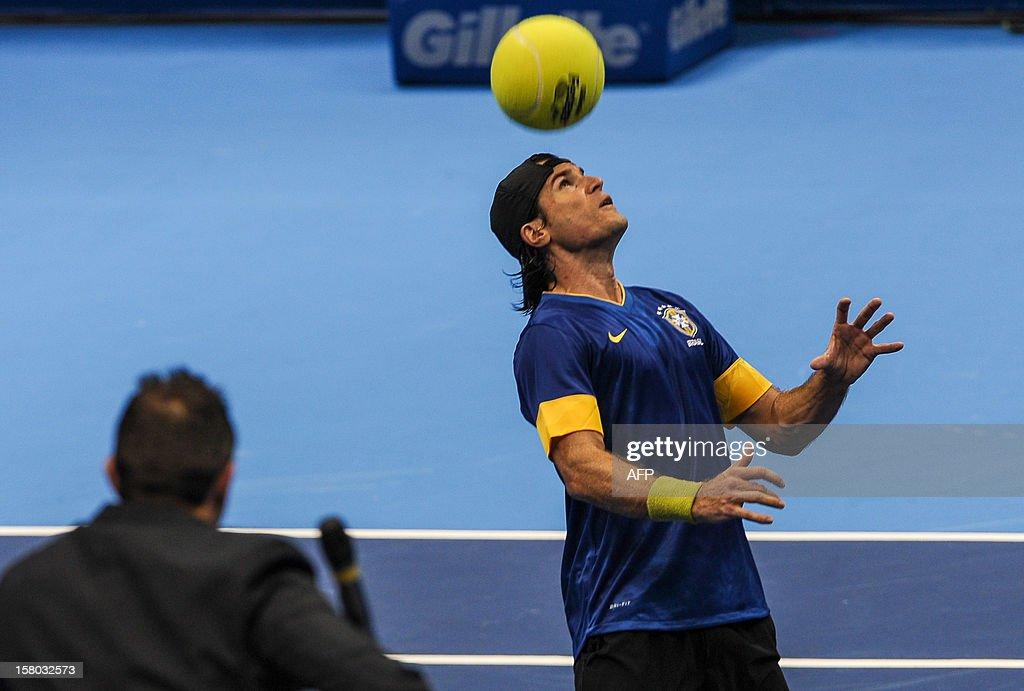 German tennis player Tommy Haas, wearing Brazilian national football team uniform, controls a giant tennis ball during an exhibition match against Swiss Roger Federer, at the Ibirapuera Gymnasium in Sao Paulo, Brazil, on December 9, 2012. AFP PHOTO/Yasuyoshi CHIBA