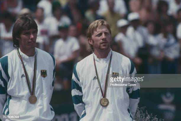 German tennis players Boris Becker and Michael Stich pictured standing together on the medal podium after finishing in first place to win the gold...