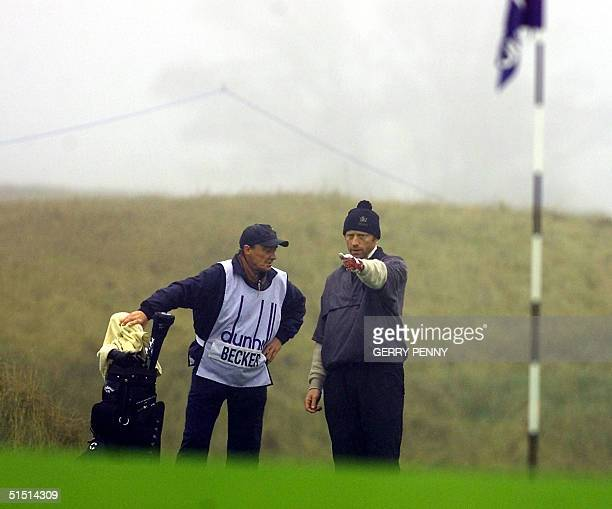 German tennis star Boris Becker discusses the lie of the land with his caddie on the 18th green at Kingsbarns Scotland 21 October 2001 in the Dunhill...