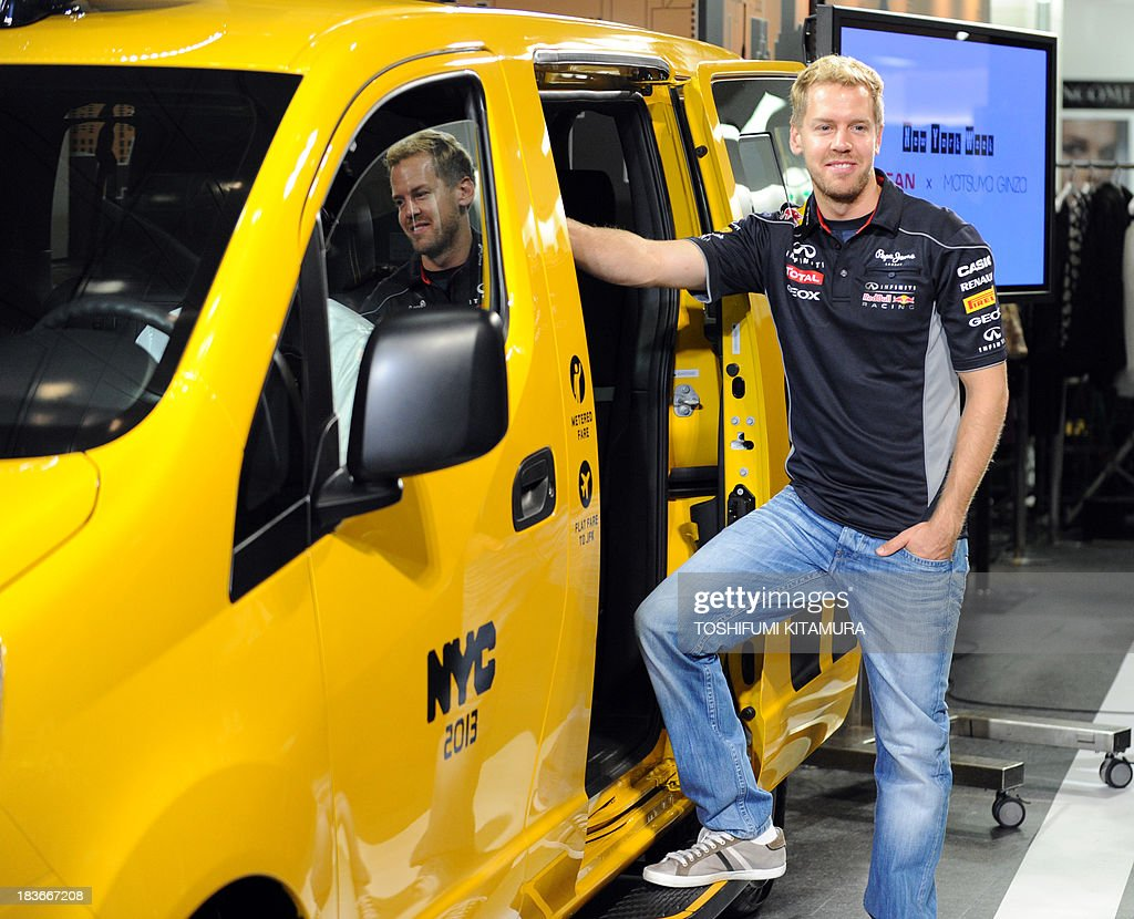 German three-time Formula One champion Sebastian Vettel poses beside Nissan's NV200, 'New York taxi of tomorrow', during its press preview in Tokyo on October 9, 2013. Nissan displays a production model of New York city's next-generation yellow cab at the Matsuya Ginza department store during the store's one-week-long New York week fair.