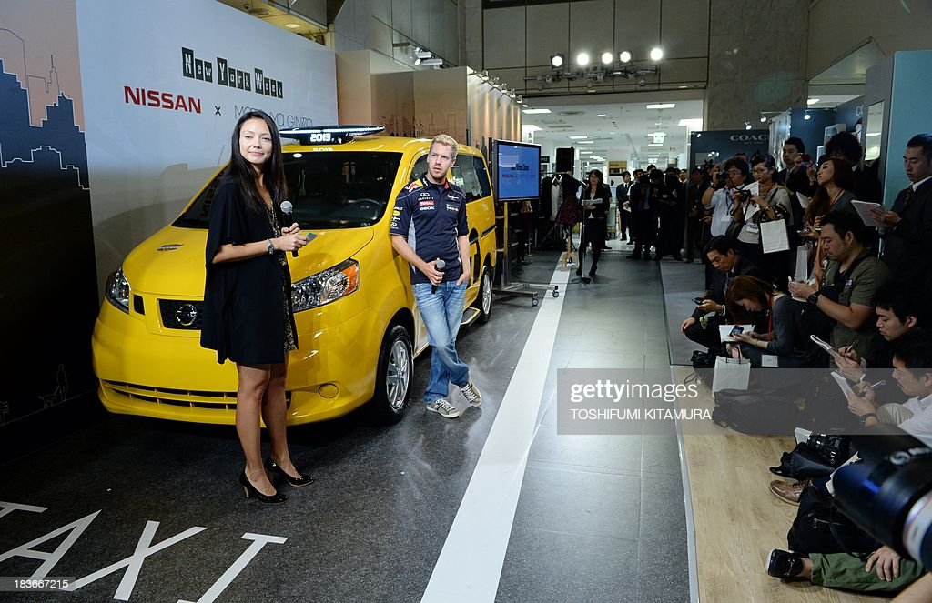 German three-time Formula One champion Sebastian Vettel (C) poses beside Nissan's NV200, 'New York taxi of tomorrow', during its press preview in Tokyo on October 9, 2013. Nissan displays a production model of New York city's next-generation yellow cab at the Matsuya Ginza department store during the store's one-week-long New York week fair.