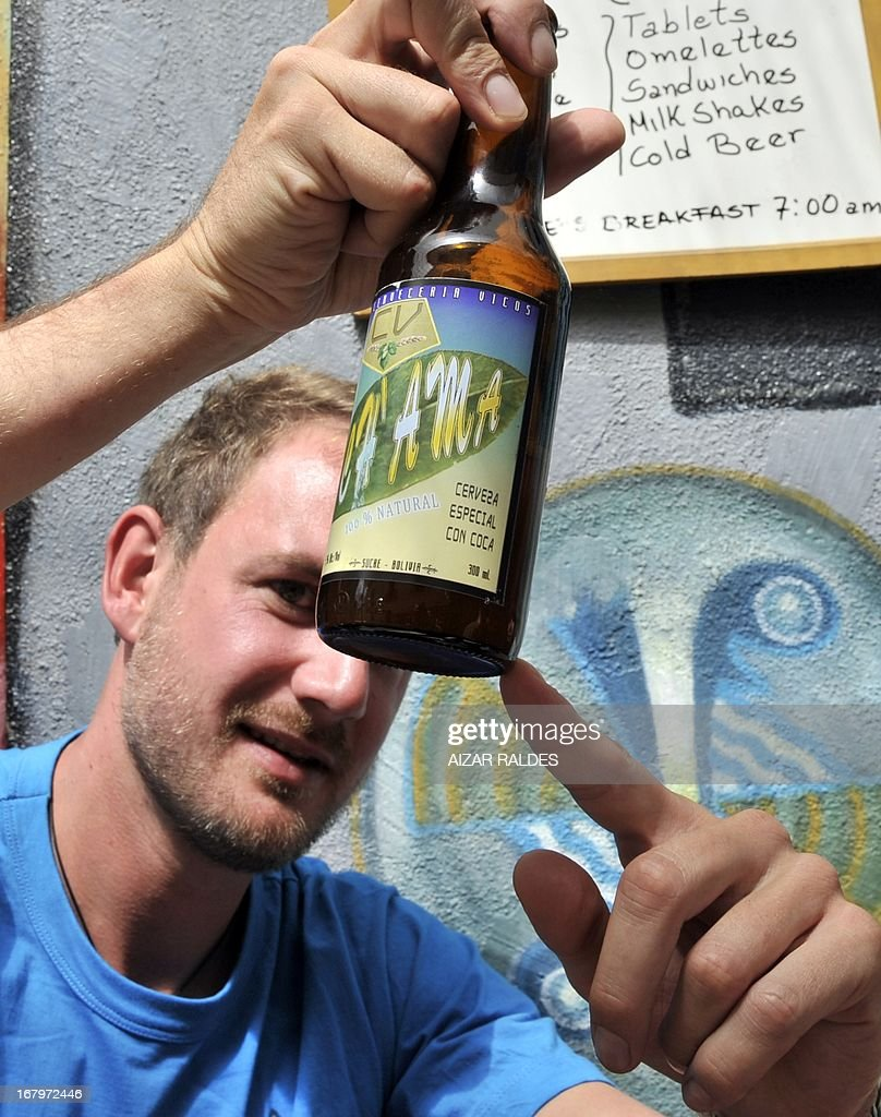 A German tourist shows a bottle of Ch'ama, a coca leaves and barley based beer in a bar in La Paz, on May 2, 2013. The beer, made with organic barley and coca, have the same alcohol content that a normal one, and is mainly consumed by European tourists. AFP PHOTO / Aizar Raldes