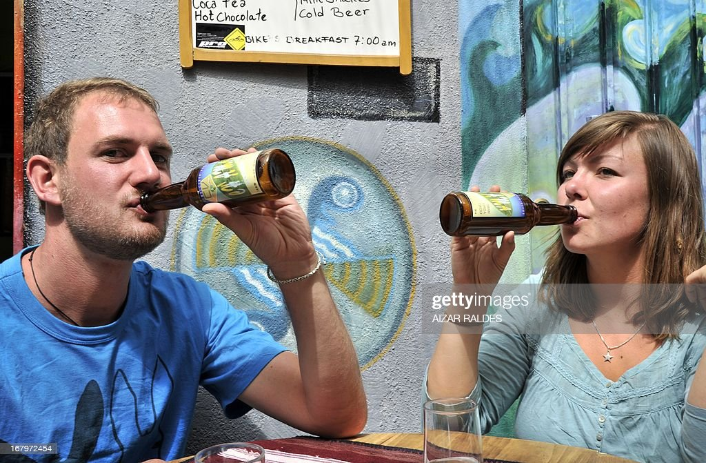German tourists drink Ch'ama, a coca leaves and barley based beer in a bar in La Paz, on May 2, 2013. The beer, made with organic barley and coca, have the same alcohol content that a normal one, and is mainly consumed by European tourists. AFP PHOTO / Aizar Raldes