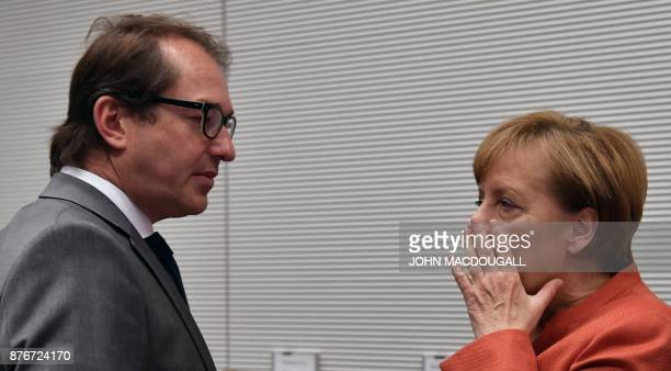 German Transport Minister Alexander Dobrindt and German Chancellor Angela Merkel speak prior to a parliamentary group meeting of the conservative...