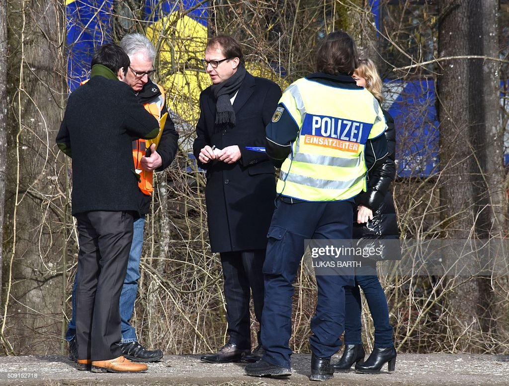 German Transport minister Alexander Dobrindt (C) chats with police officers and officials at the site of a train accident near Bad Aibling, southern Germany, on February 9, 2016. Two commuter trains collided head-on near Bad Aibling, around 60 kilometres (40 miles) southeast of Munich, killing at least nine people and injuring around 100, in what is believed to be the country's first deadly rail accident in three years. / AFP / LUKAS BARTH