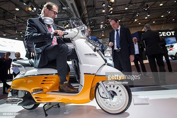 German Transport Minister Alexander Dobrindt sit on a Peugeot scooter Django at the 2014 AMI Auto Show on May 30 2014 in Leipzig Germany The show...