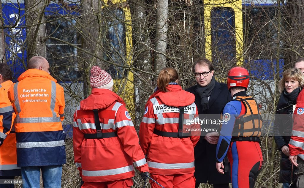 German Transport Minister Alexander Dobrindt (3rd R) speaks to Search-rescue team workers at the two trains' collision site after two commuter trains collied on a route, close to Bad Aibling, approximately 60 kilometers (40 miles) southeast of Munich, Germany on February 09, 2016. At least 8 killed and several others injured after the collision, reported.