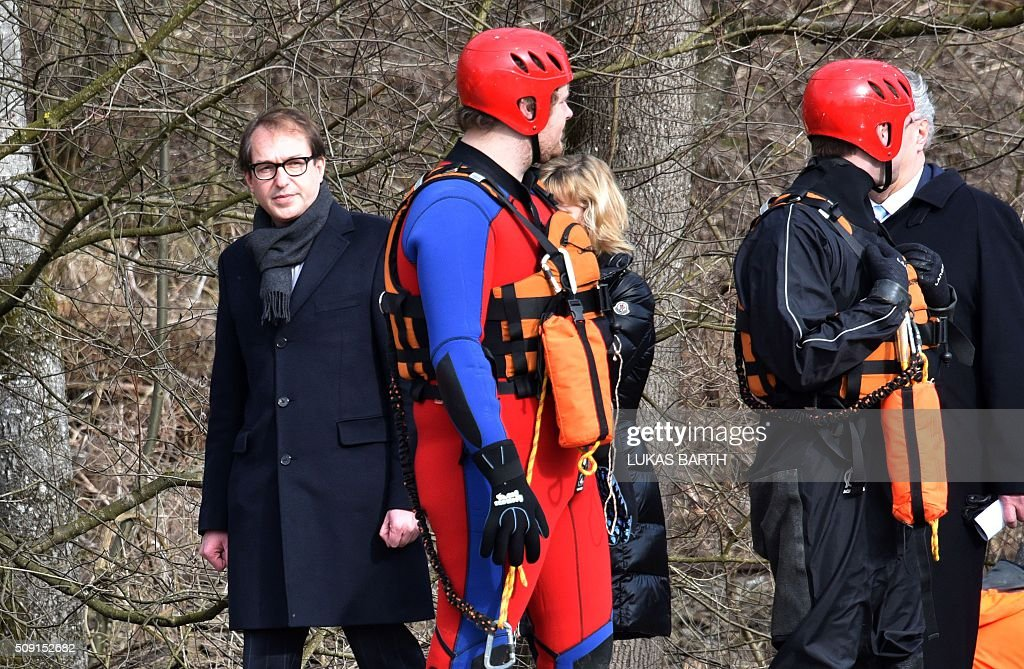 German Transport minister Alexander Dobrindt (L) walks by emergency rescuers at the site of a train accident near Bad Aibling, southern Germany, on February 9, 2016. Two commuter trains collided head-on near Bad Aibling, around 60 kilometres (40 miles) southeast of Munich, killing at least nine people and injuring around 100, in what is believed to be the country's first deadly rail accident in three years. / AFP / LUKAS BARTH