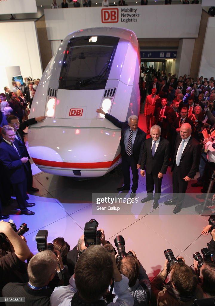 German Transport Minister <a gi-track='captionPersonalityLinkClicked' href=/galleries/search?phrase=Peter+Ramsauer&family=editorial&specificpeople=770626 ng-click='$event.stopPropagation()'>Peter Ramsauer</a> (just R of train) and Deutsche Bahn head Ruediger Grube (R of Ramsauer) unveil a mockup of the ICx, the latest generation of Deutsche Bahn high-speed trains, at the Innotrans 2012 railway trade fair on September 18, 2012 in Berlin, Germany. Grube said the new train delivers 30% better fuel efficiency.