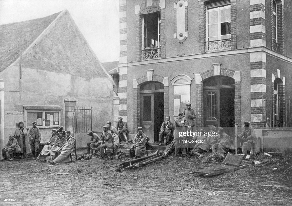 German troops sitting on the steps of the Vareddes Town Hall, France, 1914. German soldiers taking a rest during the First Battle of the Marne.