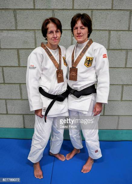 German twin sisters Carmen and Ramona Brussig who are both 40 with each holding a Paralympic gold medal pose wearing their bronze medals that they...