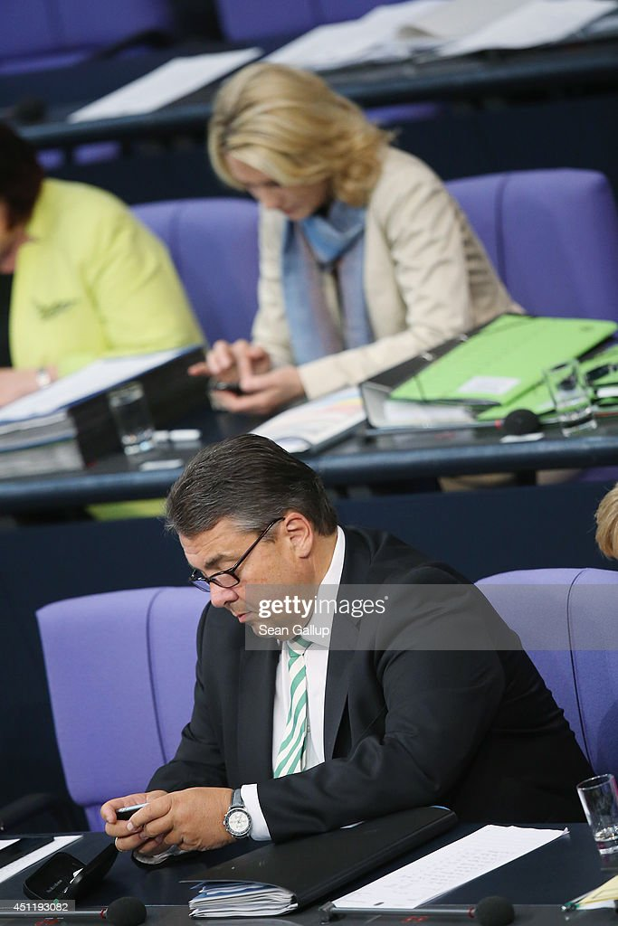 German Vice Chancellor and Economy and Energy Minister <a gi-track='captionPersonalityLinkClicked' href=/galleries/search?phrase=Sigmar+Gabriel&family=editorial&specificpeople=543927 ng-click='$event.stopPropagation()'>Sigmar Gabriel</a>, who is also Chairman of the German Social Democrats (SPD), and Family Minister Manuela Schwesig type on smartphones during debates at the Bundestag over the Chancellery budget on June 25, 2014 in Berlin, Germany. The Bundestag will resume hearings this week into the activities of the U.S. National Security Agency (NSA) in Germany and is scheduled to question two former NSA employees. Revelations last year that the NSA had been eavesdropping on the mobile phone of German Chancellor Angela Merkel and other leading government members for years caused an uproar in Germany and strained U.S.-German relations.