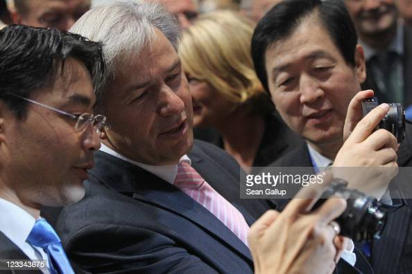 German Vice Chancellor and Economy Minister Philipp Roesler and Berlin city Mayor Klaus Wowereit check out a Samsung digital camera as Samsung Vice...