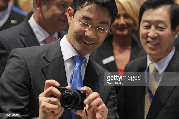 German Vice Chancellor and Economy Minister Philipp Roesler checks out a Samsung NX 2000 digital camera as Samsung Vice Chairman and CEO GeeSung Choi...