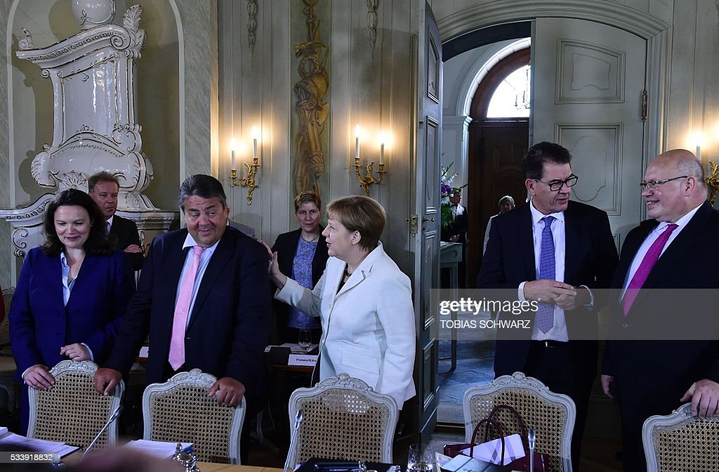 German Vice Chancellor, Economy and Energy Minister Sigmar Gabriel (2nd L) and German Chancellor Angela Merkel (C) arrives with other participants of a closed meeting of the German cabinet at Meseberg Palace on May 24, 2016 in Meseberg, northeastern Germany. / AFP / TOBIAS
