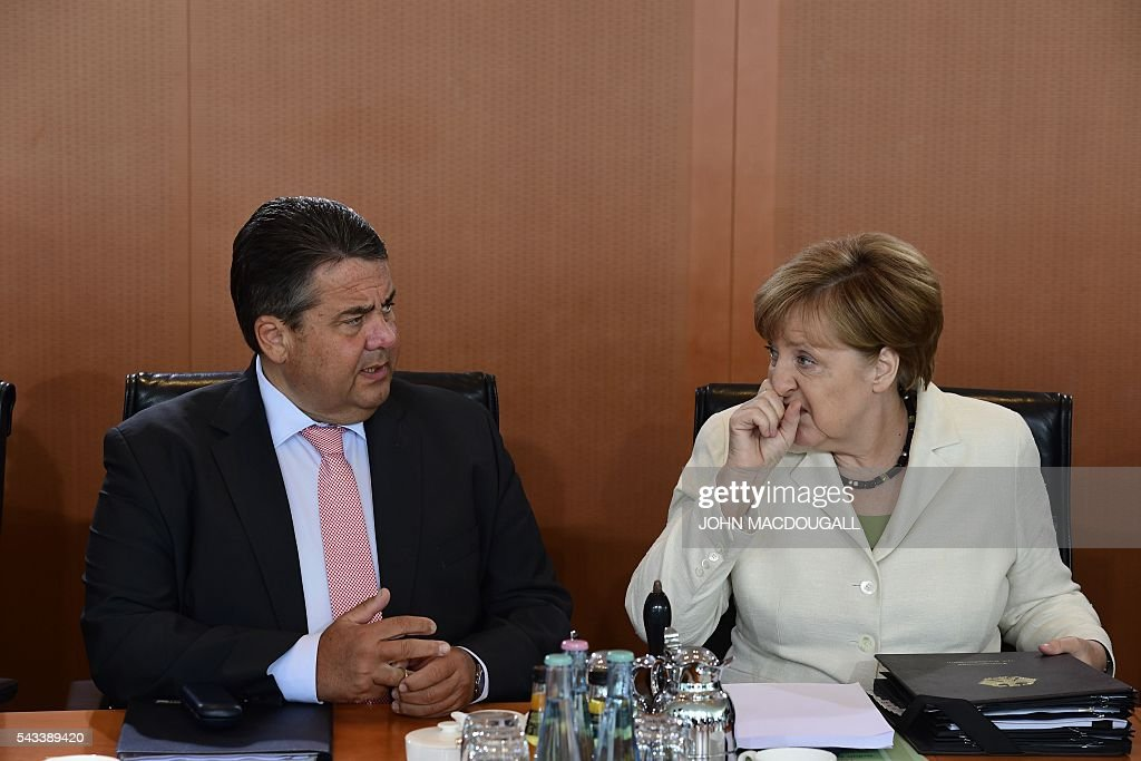 German Vice Chancellor, Economy and Energy Minister Sigmar Gabriel (L) and German Chancellor Angela Merkel chat upon arrival at German govermnent cabinet meeting at the chancellery in Berlin on June 28, 2016. / AFP / John MACDOUGALL