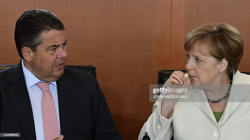 German Vice Chancellor, Economy and Energy Minister Sigmar Gabriel(L) and German Chancellor Angela Merkel chat upon arrival at German govermnent cabinet meeting at the chancellery in Berlin on June 28, 2016. / AFP / John MACDOUGALL