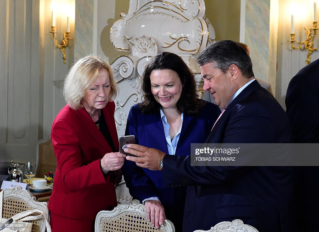 German Vice Chancellor, Economy and Energy Minister Sigmar Gabriel (R), German Education and Research Minister Johanna Wanka (L) and German Labour and Social Minister Andrea Nahles look at the cell phone during a closed meeting of the German cabinet at Meseberg Palace on May 24, 2016 in Meseberg, northeastern Germany. / AFP / TOBIAS