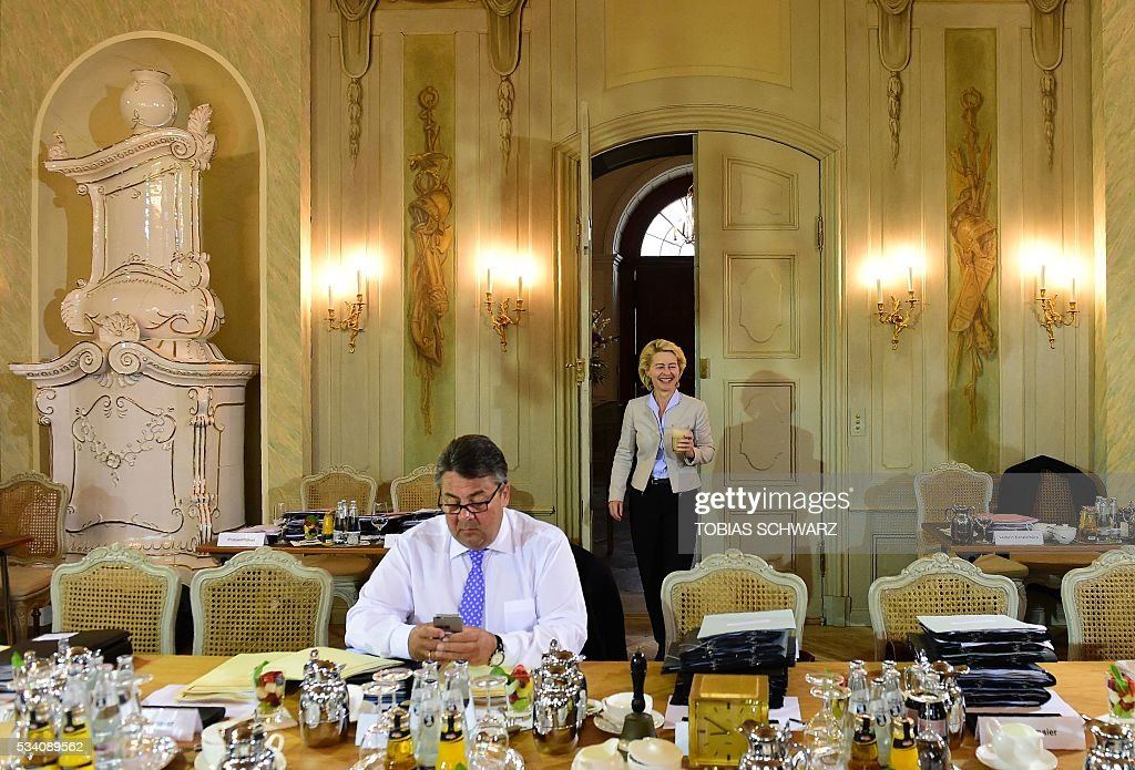 German Vice Chancellor, Economy and Energy Minister Sigmar Gabriel (L) checks his mobile device as German Defence Minister Ursula von der Leyen arrives for the weekly cabinet meeting taking place in the framework of a retreat meeting of the German cabinet at Meseberg Palace on May 25, 2016 in Meseberg near Gransee, northeastern Germany. / AFP / TOBIAS