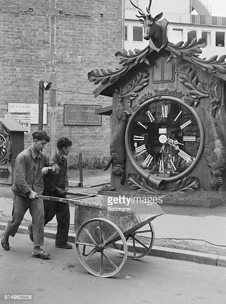 A German workman checks his watch with the world's biggest cuckoo clock which is located at Wiesbaden Germany The clock frame is actually the outside...