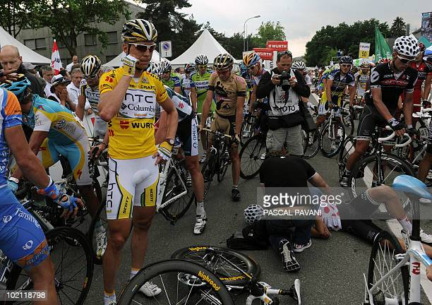 German yellow jersey leader Tony Martin stands by an injured cyclist who crashed near the finish line during the fourth stage Schawarzenburg...
