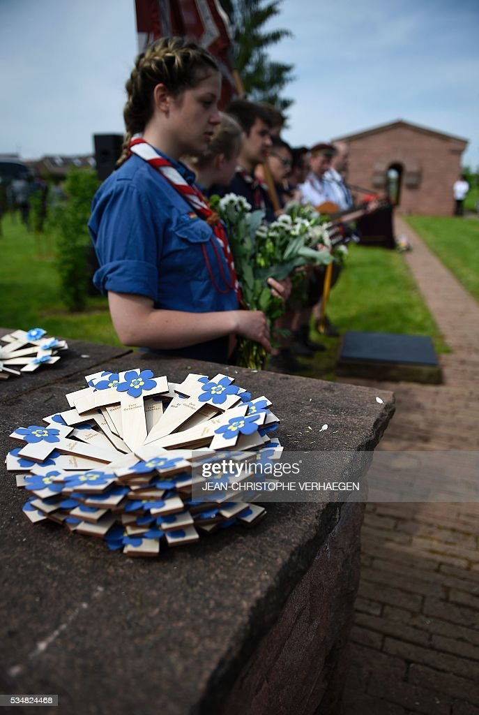 German youths play music on May 28, 2016 at the German WWI cemetary in Romagne-sous-Montfaucon, eastern France, during the burial of Hans Winckelmann, a WWI German soldier, as part of the 100-year commemoration of WWI's Battle of Verdun. / AFP / JEAN