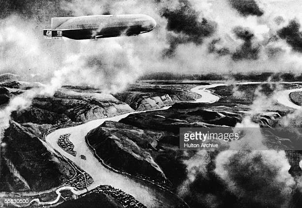 A German zeppelin dirigible flies over a river cutting through the rugged Balkan terrain littered with smoldering fires during World War I 1910s To...