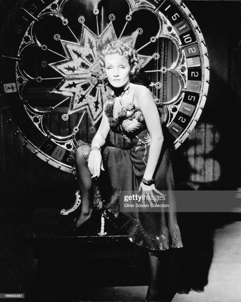 German-American actress Marlene Dietrich (1901 - 1992) as Frenchy, standing by a large roulette wheel in a publicity still for 'Destry Rides Again', directed by George Marshall, 1939.