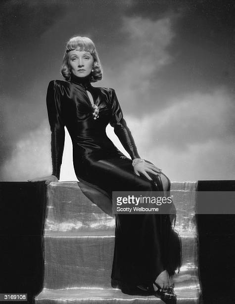 Germanborn actress Marlene Dietrich wearing a dark satin gown and curled fringe for the film 'Manpower' Costumes by Milo Anderson