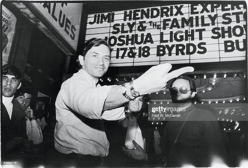 Germanborn America concert promoter Bill Graham smiles as he extends his middle to the camera while he and assorted patrons stand under the marquee...