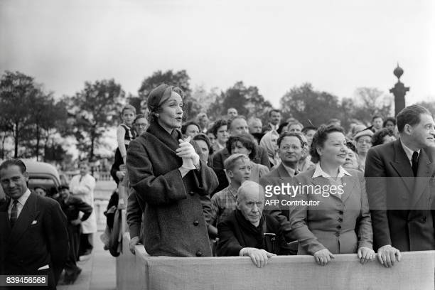 Germanborn American actress Marlene Dietrich attends the military parade of the official ceremony marking the 10th anniversary of the Paris'...
