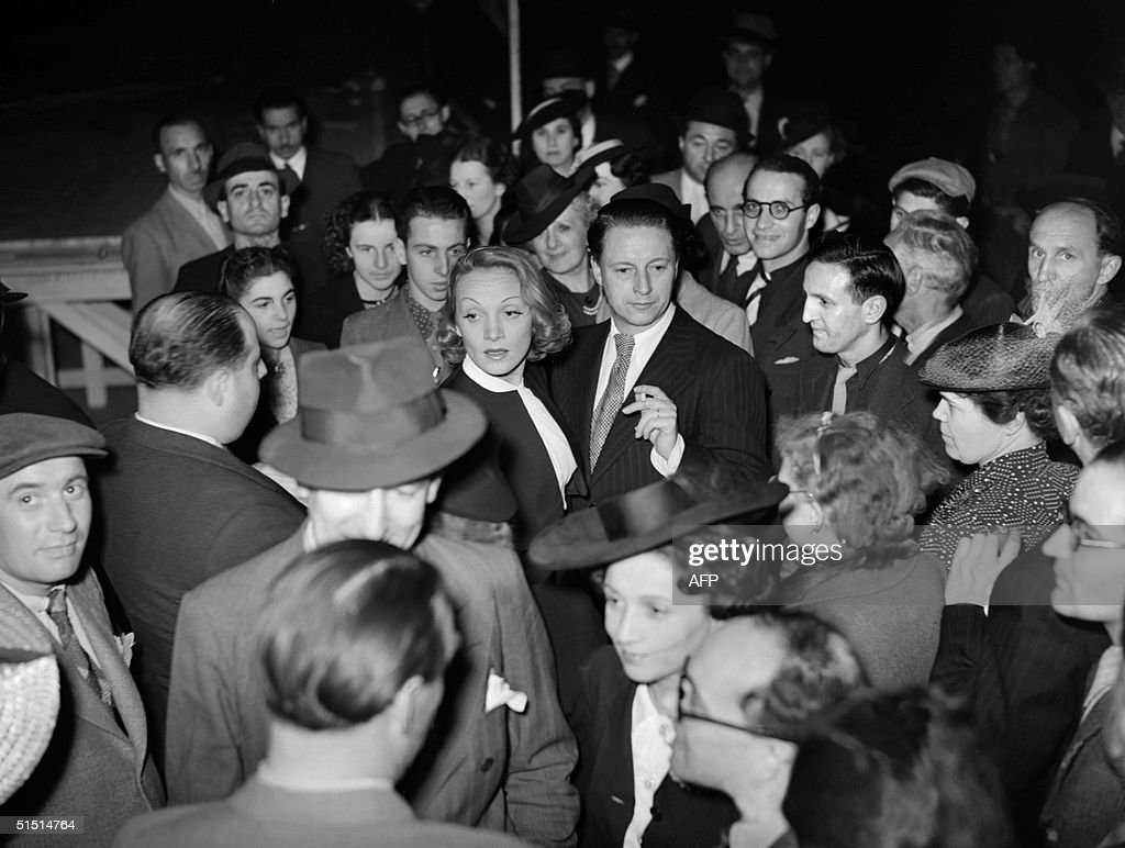 German-born American actress Marlene Dietrich (C), is surrounded by fans 14 July 1939 during the Bastille Day ball at Paris Opera Square. Marlene Dietrich, originally Maria Magdalene von Losch (1904-92), became famous in von Sternberg's 'Der Blaue Engel' (1930, The Blue Angel), and developed a glamourous and sensual film personality in such Hollywood films as 'Morocco' (1930) and 'Blond Venus' (1932). During World War II she often appeared in shows for Allied troops, and continued to make films after the War. Dietrich also became an international cabaret star.
