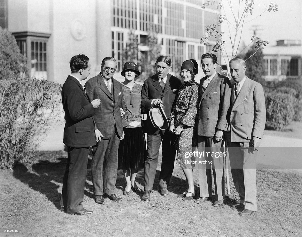 German-born writer and producer Paul Bern (1889 - 1932), Russian-born producer Louis B. Mayer (1885 - 1957), American actor Aileen Pringle (1895 - 1989), American journalist H. L. Mencken (1880 - 1956), Canadian-born actress Norma Shearer (1900 - 1983), and American producers Irving Thalberg (1899 - 1936) and Harry Rapf, talk on the MGM studio lot, circa 1930.