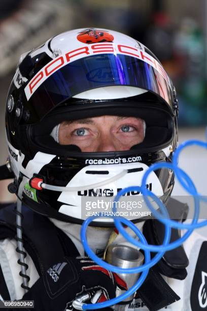 German's driver Andre Lotterer competing with the Porsche 919 Hybrid N°1 looks on as he freshes himslef up with a fan in his pit during the 85th Le...