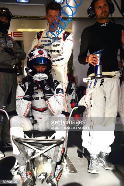 German's driver Andre Lotterer competing with the Porsche 919 Hybrid N°1 looks on as he sits in his pit during the 85th Le Mans 24hours endurance...