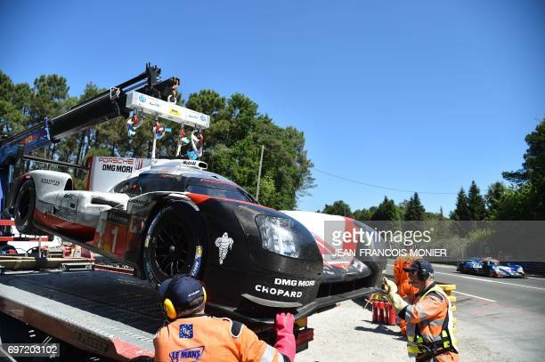 German's driver Andre Lotterer's Porsche 919 Hybrid N°1 is brought back to the stands after it was abandoned due to an oil pressure problem during...